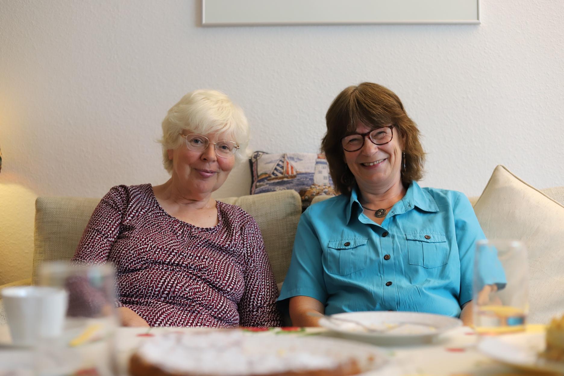 Zwei Frauen sitzen auf einem Sofa im Wohnzimer und lächeln in die Kamera.