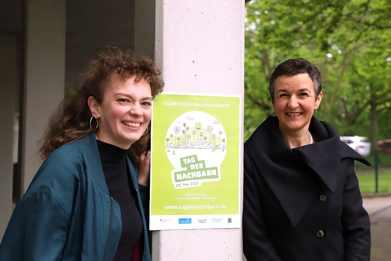 Mitarbeiterinnen Sira Eberlin und Bea Schramm mit dem Plakat zum Tag der Nachbarn vor einer Säule