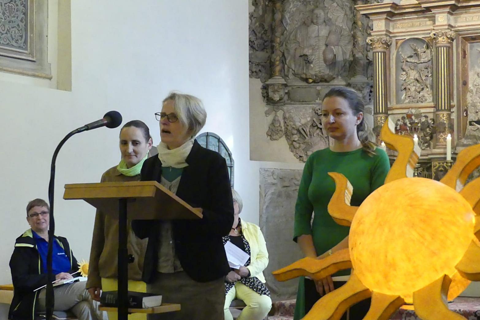 Drei Frauen stehen am Pult und sprechen