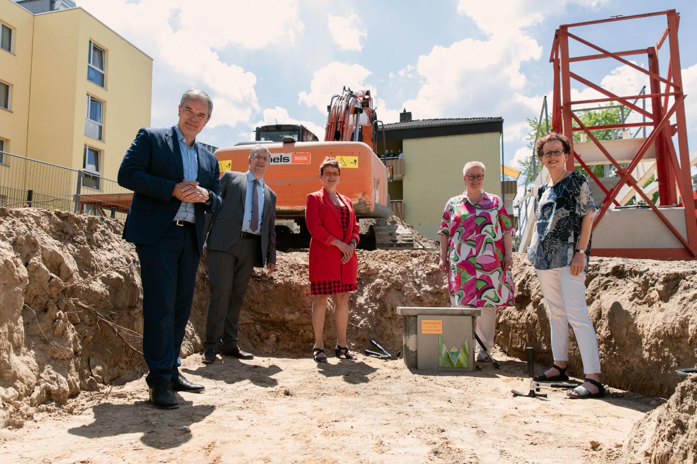 zwei Männer und drei Frauen in einer Baugrube vor einem Grundstein